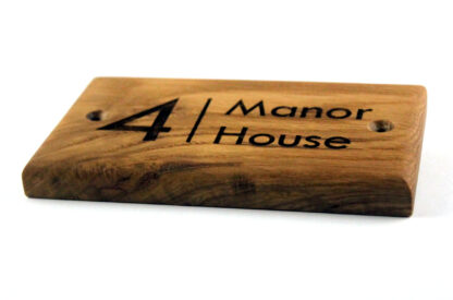 A solid oak wooden sign with rounded edges.