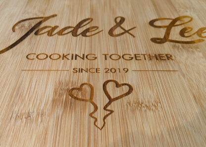 Close up of heart chopping board text with cursive text saying Jade & Lee then in a standard font saying cooking together since 2019 and two hearts.
