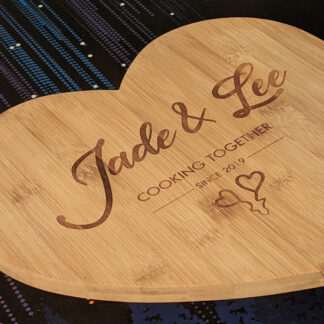 Personalised Heart Chopping Board side view with the text Jade and Lee in cursive and then cooking together since 2019 with hearts below.