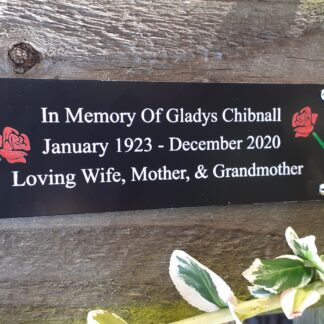 Memorial plaque attached to a wooden fence with bush near by.