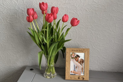 Picture frame standing on draws next to flowers