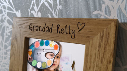 Close up on top part of picture frame with name and heart